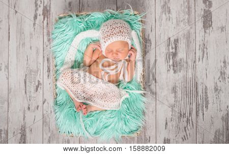 funny sleeping newborn in panties and hat on a cot with turquoise blanket, top view