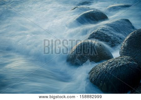 Waves swelling over rocks on the shore. Long exposure.