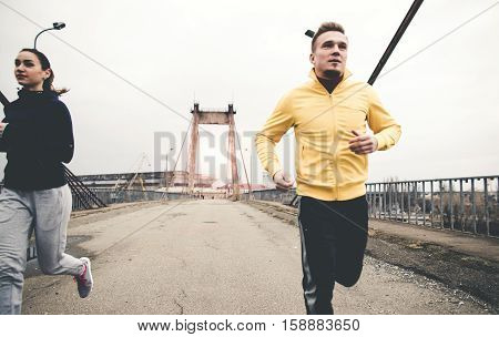 Couple of young runners in sportswear running on city bridge road. Healthy lifestyle