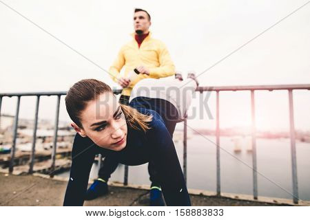 Beautiful young women in sports clothing training on a city bridge on the sunset