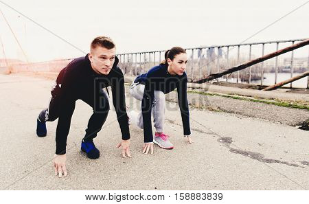 Couple athletes are at a low start on city bridge road. Healthy lifestyle