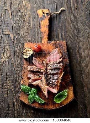 grilled beef steak on a cutting board on a wooden background