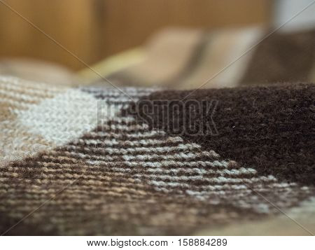 Selective focus on brown blanket texture close up. Blanket texture pattern against blurred bright background.
