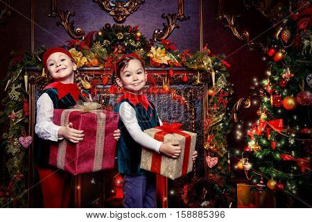 Santa Claus's helpers. Two cute children in christmas elf costumes in a room beautifully decorated for Christmas. Time of miracles. Gifts from Santa Claus.