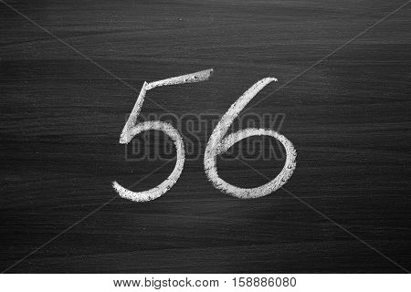 number fifty six enumeration written with a chalk on the blackboard
