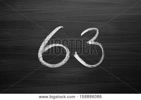 number sixty three enumeration written with a chalk on the blackboard
