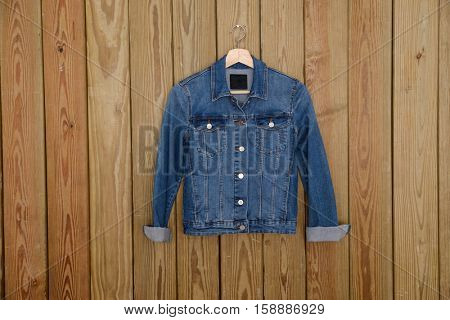 A blue denim shirt is on clothes-hanger on wooden background