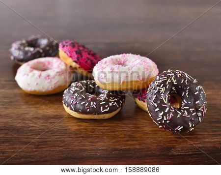 Heap of fresh donuts with glaze on a wooden table. Delicious unhealthy food. Multicolored glazed donuts with chocolate sprinkles.