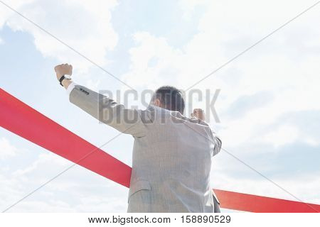 Rear view of businessman crossing finish line against sky