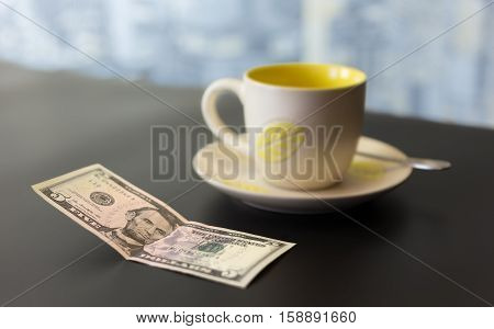 concept of a five dollar tip on a dark table with a blurred background