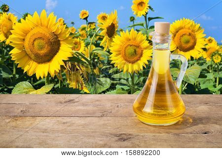 sunflower oil. Sunflower oil in glass bottle on wooden table on the background of the sunflower field. Sunflower field with blue sky. Photo with copy space area for a text