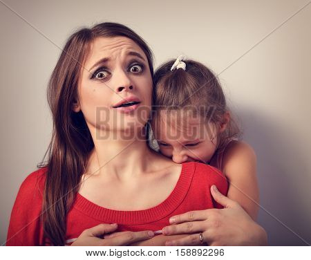 Angry Emotional Kid Girl Wanting To Bite And Terroring Her Shocked Bushed Frightened Mother With Big