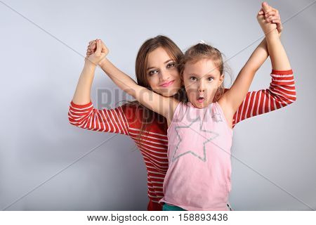Playful Mother And Crazy Joking Grimacing Kid Holding Each Other By The Hands On Blue Background