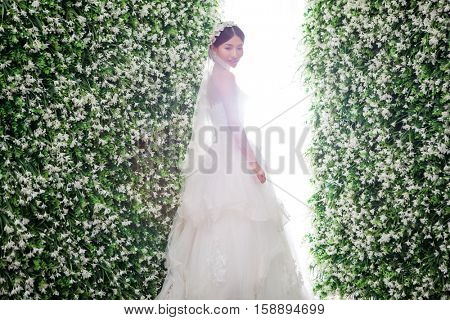 Side view of shy bride standing amidst flower decorations