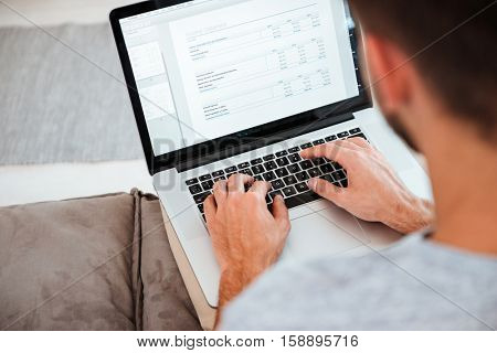 Cropped image of a young man typing on his laptop while sitting on sofa. Focus on hands typing.
