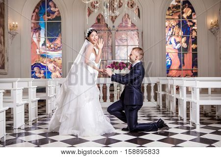 Side view of bridegroom putting ring on surprised bride's finger in church
