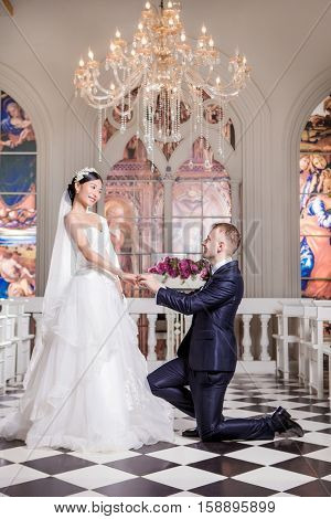Side view of bridegroom putting ring on happy bride's finger in church