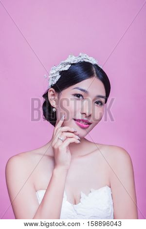 Portrait of beautiful bride with hand on chin against pink background
