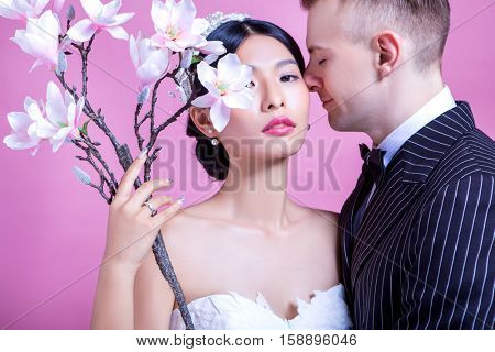 Portrait of confident bride with loving bridegroom against pink background