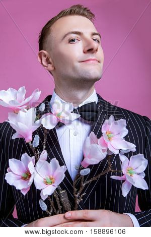 Portrait of confident bridegroom holding artificial flowers while standing against pink background