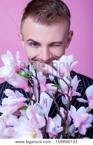 Portrait of bridegroom with artificial flowers winking against pink background