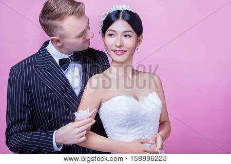 Loving bridegroom holding flower while looking at bride against pink background