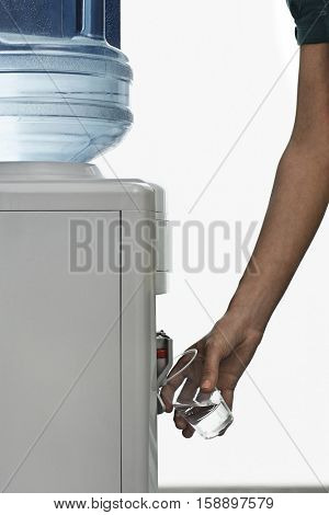 Closeup side view of a young man pouring water from cooler