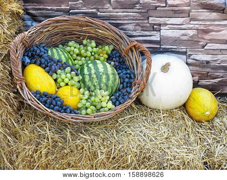 fruit basket with melon watermelon and grapes on straw