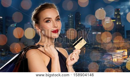 people, luxury and sale concept - beautiful woman with credit card and shopping bags over singapore city and holidays lights background