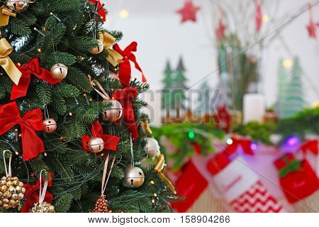 Christmas tree decorated with jingle bells, bows and garland, close up view