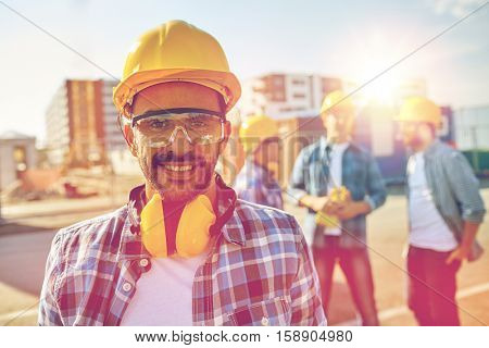 business, building, teamwork and people concept - smiling builder with hardhat and headphones over group of smiling builders at construction site