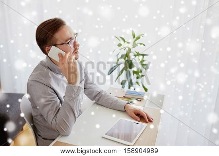 business, startup, technology, communication and people concept - businessman or creative male worker with computer calling on smarphone at home office over snow