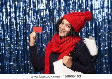 Smiling young woman in red winter hat and scarf carrying a pair of ice skates and showing blank credit card over blue glittery background