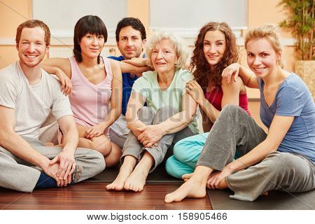 Yoga group with senior woman relaxing after class in studio