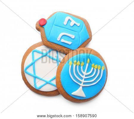 Tasty glazed cookies for Hanukkah, on white background