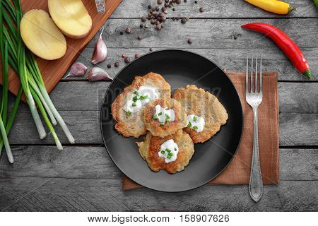 Plate with tasty potato pancakes for Hanukkah and some ingredients on wooden table