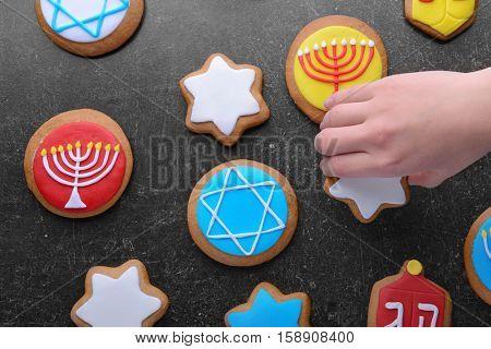 Female hand taking tasty glazed cookie for Hanukkah from dark grunge table