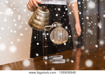 equipment, coffee shop, people and technology concept - close up of woman with pot pouring hot water to coffeemaker filter at cafe bar or restaurant kitchen over snow