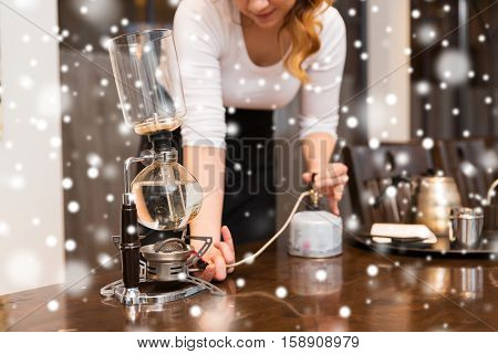 equipment, coffee shop, people and technology concept - close up of woman with butane gas burner heating water in siphon coffeemaker at cafe bar or restaurant kitchen over snow