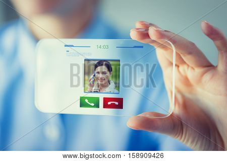 business, technology, communication and people concept - close up of woman hand holding and showing transparent smartphone with incoming video call icon on screen