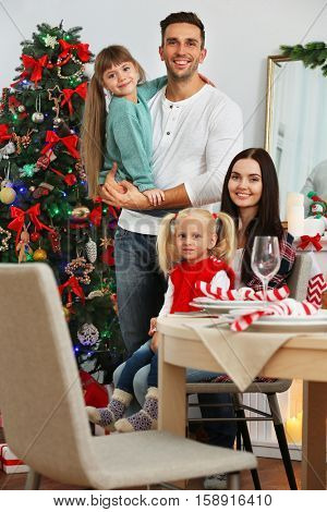 Happy family preparing for Christmas dinner in living room