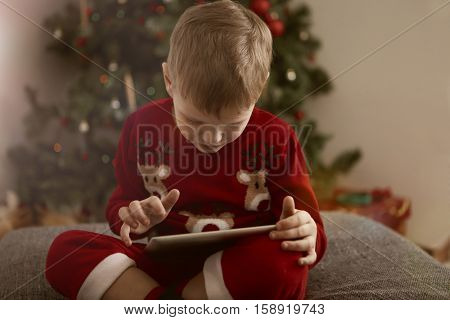 Young boy using his tablet during Christmas