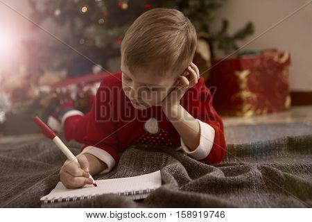 Boy writing next to the Christmas tree