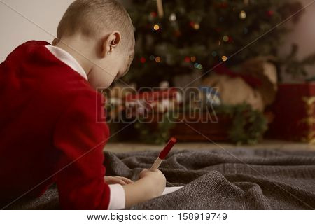 Child writing down what she wishes for Christmas