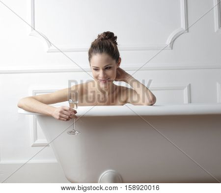 Girl enjoying a bath with a glass of champagne