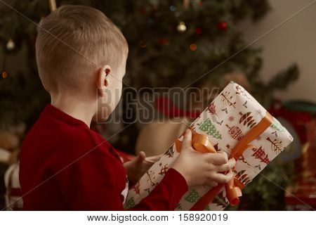 Boy guessing his present under the Christmas tree