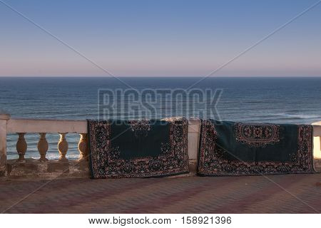 Like after a magic carpet ride carpets getting dry hanging on the fence. Atlantic ocean in the background. City Sidi Ifni Morocco.