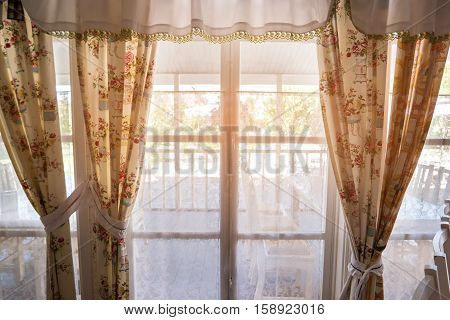 Window and curtains. Porch behind the window. Go meet the summer. Spend holidays at home.