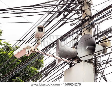 CCTV camera security and vintage horn speaker with cables and wires on pole / White background