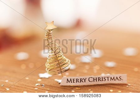 Merry Christmas background with Christmas tree made from gold or brass wires and star glitter.